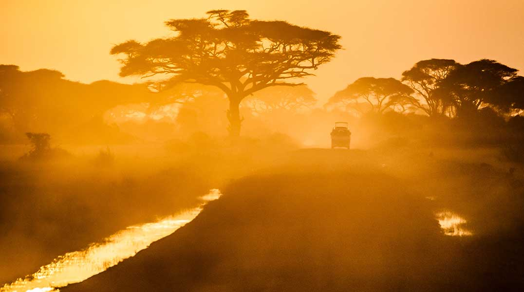 Safety-&-Etiquette safari vehicle at sunset on a dusty road