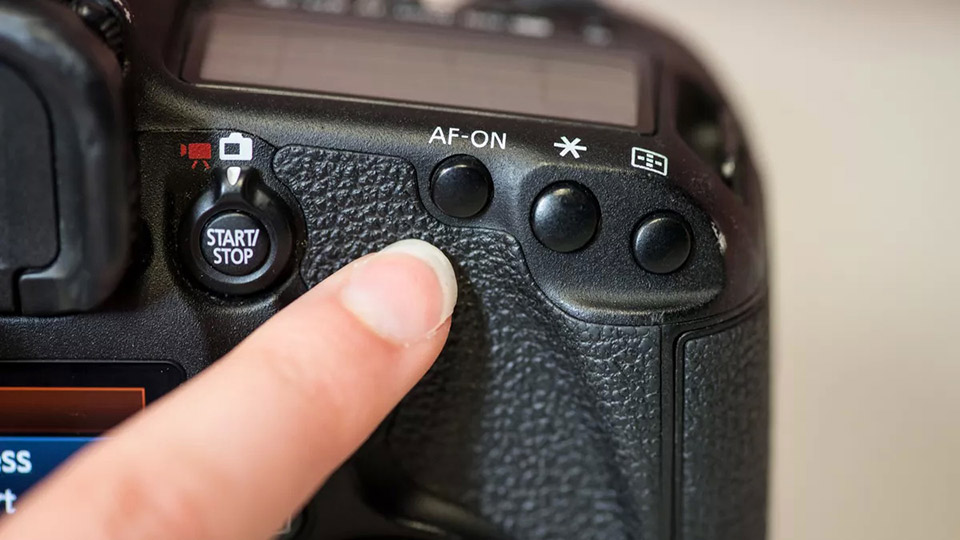Back Button Focus- Finger pointing at buttons on a camera